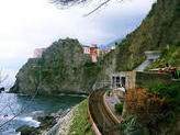 Featured Travel Photo - Our view while walking towards the second village Manarola (I believe). See the train track below and the cute houses peeking from beneath the cliffs?
